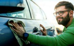 A imagem mostra um homem passando o pano no carro. Foto para ilustrar o exto sobre como valorizar o seu carro